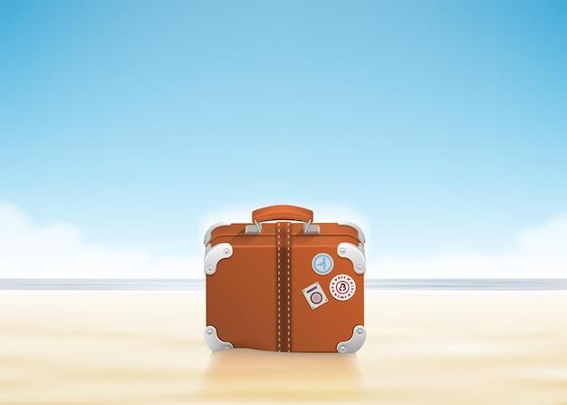 Bagagem com adesivos de viagem na praia ensolarada.