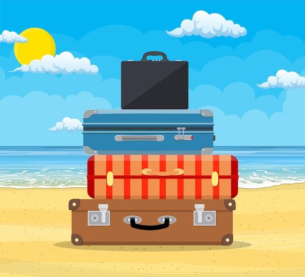 Bagagens, malas, malas com ícones de viagens e objetos na praia