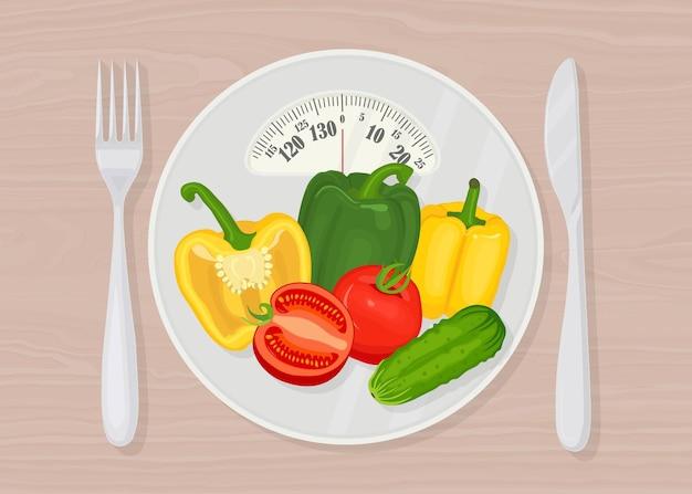 Balança com legumes, garfo e faca. dieta e saúde