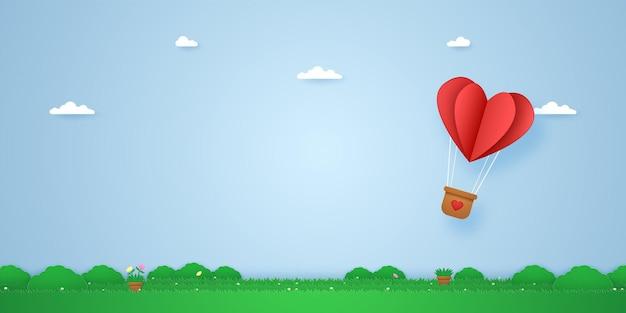 Balão de ar quente com coração dobrado vermelho voando sobre a grama em estilo de arte em papel