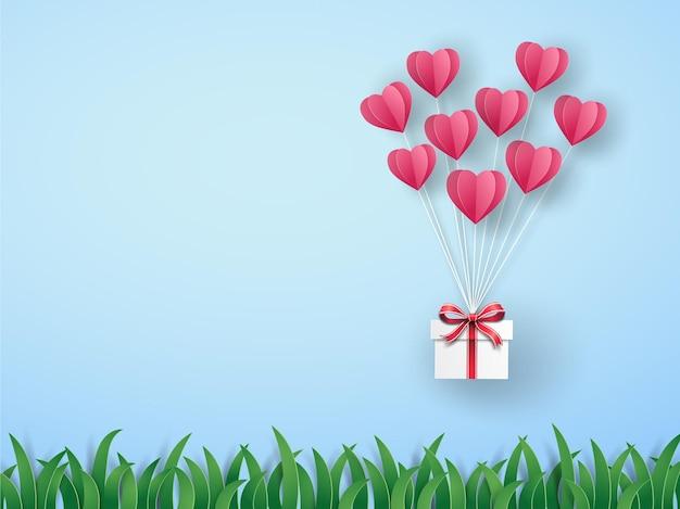 Balão de ar quente de origami rosa em forma de coração com caixa de presente voando no céu sobre o prado verde.