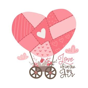 Balão de ar quente de retalhos em forma de coração com cesto cheio de flores.