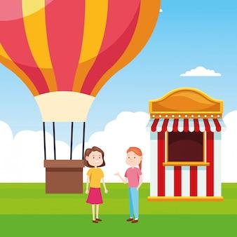 Balão de ar quente e duas mulheres em pé ao lado da bilheteria sobre a paisagem