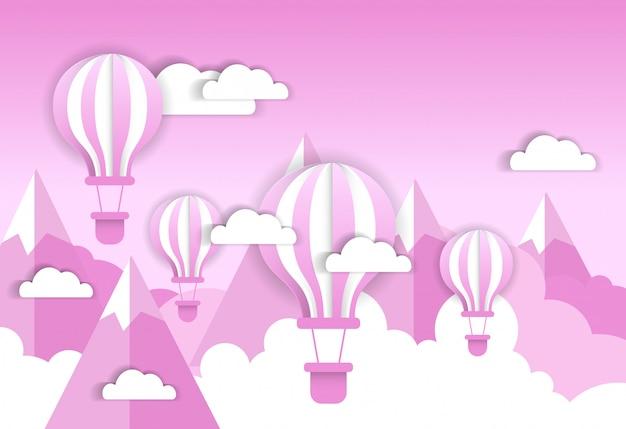 Balão de ar retrô sobre nuvens cor de rosa e montanhas