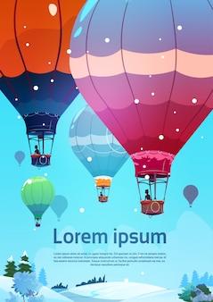 Balões de ar coloridos que voam no céu sobre a paisagem da neve do inverno