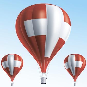 Balões de ar quente pintados com a bandeira da suíça