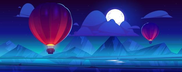 Balões de ar voando no céu noturno com lua cheia e nuvens nas montanhas
