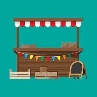 Banca de comida do mercado com bandeiras, caixas, quadro de giz