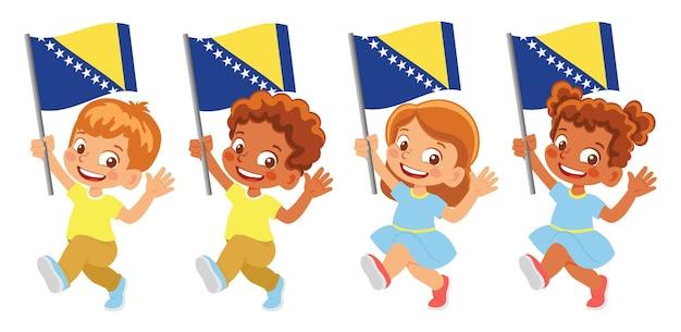 Bandeira da bósnia e herzegovina na mão. crianças segurando uma bandeira. bandeira nacional da bósnia e herzegovina