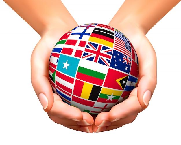 Bandeiras do mundo no globo e mãos.
