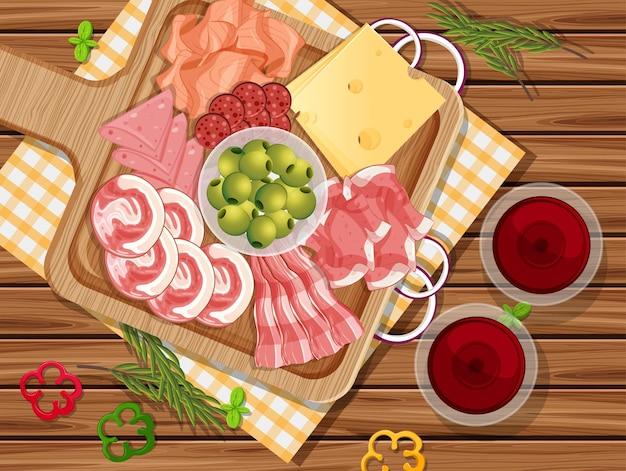 Bandeja de charcutaria e carnes defumadas no fundo da mesa de madeira