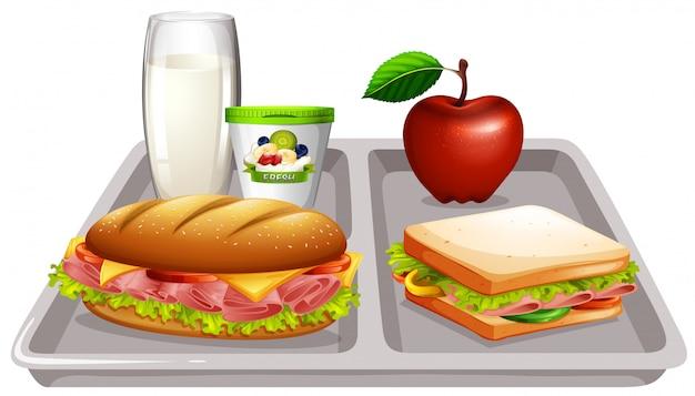 Bandeja de comida com leite e sanduíches