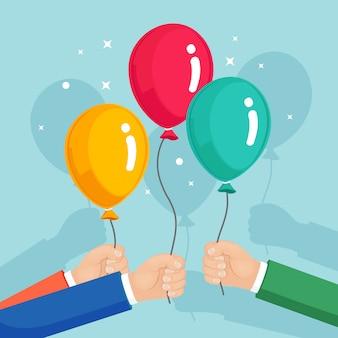 Bando de balão de hélio na mão, voando com bolas de ar no fundo branco. feliz aniversário, conceito de férias. decoração de festa. desenho animado