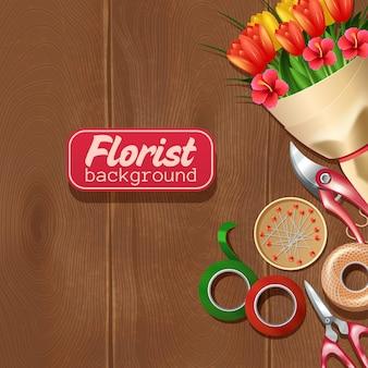 Bando de equipamentos e flores de florista em fundo de madeira