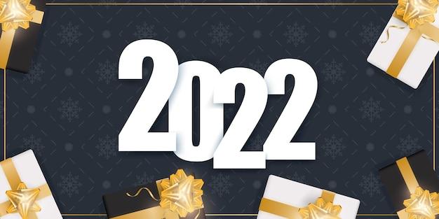 Banner de ano novo de 2022 com caixas de presente, fitas douradas e arco.