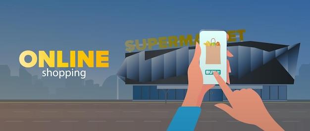 Banner de compras online. peça comida em casa. mão segura o smartphone.