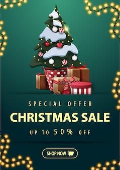 Banner de desconto de oferta especial com guirlanda, botão e árvore de natal em uma panela com presentes