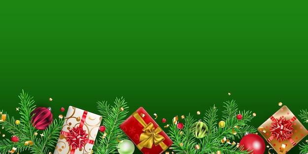Banner de natal com galhos de pinheiro, bolas, pedaços de serpentina e caixas de presente em fundo verde. repetição horizontal.