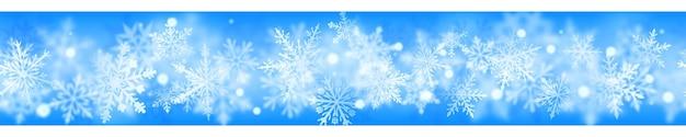 Banner de natal de flocos de neve claros e desfocados complexos em cores brancas sobre fundo azul claro
