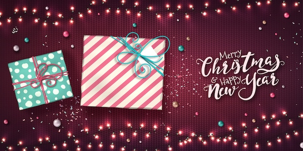 Banner de natal e ano novo com caixas de presente, guirlandas de natal de luzes, enfeites e confetes de glitter na textura de malha roxa