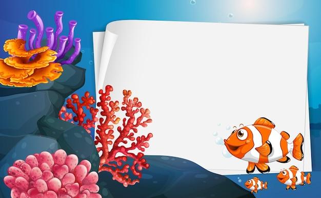 Banner de papel em branco com peixe-palhaço e elementos da natureza submarina no fundo subaquático
