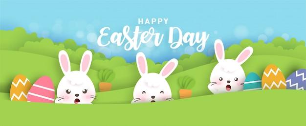 Banner de páscoa com coelhos bonitos e ovos de páscoa em estilo de corte e artesanato de papel.