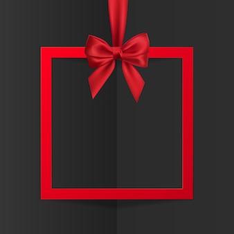 Banner de quadro de caixa de presente de feriado brilhante pendurado com fita vermelha e laço de seda em fundo preto.