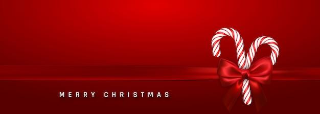 Banner de saudação de natal com bastão de doces e laço e fita vermelhos