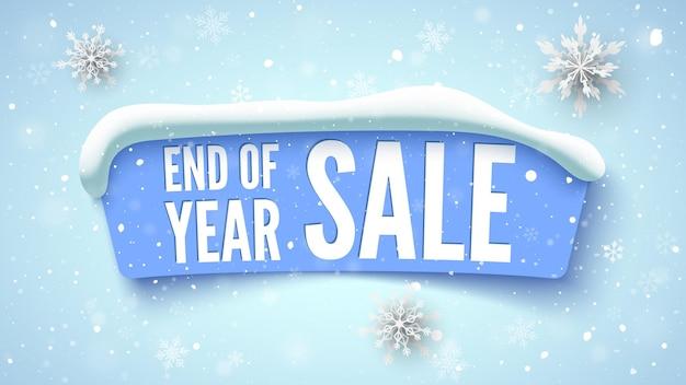 Banner de venda de final de ano azul com tampa de neve e flocos de neve