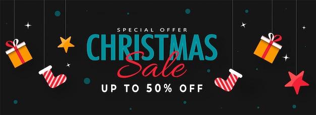 Banner de venda de natal com meias e caixas de presente, pendurado no preto.