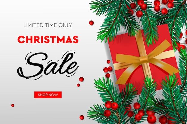 Banner de venda de natal. galhos de pinheiro realistas com bagas e uma caixa de presente vermelha