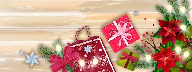 Banner de vetor de venda de inverno natal com caixas de presente de natal, sacola de compras, poinsétia, vista de mesa