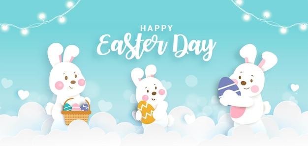 Banner do dia da páscoa com coelhos fofos e ovos de páscoa no estilo corte de papel