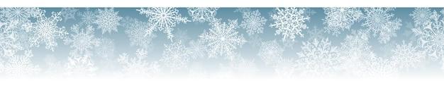 Banner horizontal de natal de grandes e pequenos flocos de neve complexos com repetição horizontal perfeita, em cores azuis claras. fundo de inverno com neve caindo