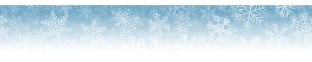 Banner horizontal sem costura de natal de muitas camadas de flocos de neve de diferentes formas, tamanhos e transparência. no fundo gradiente de azul claro para branco.