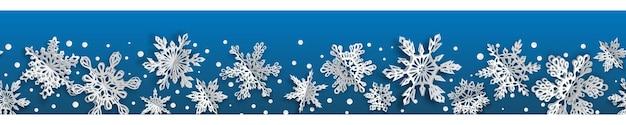 Banner sem costura de natal com flocos de neve de papel de volume com sombras suaves sobre fundo azul. com repetição horizontal