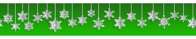 Banner sem costura de natal com flocos de neve de papel de volume com sombras suaves sobre fundo verde. com repetição horizontal