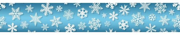 Banner sem costura horizontal de natal de flocos de neve de diferentes formas e tamanhos, com sombras. branco em azul claro.