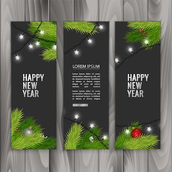 Banners de natal com ramos de pinheiro decorados com fitas, bolas vermelhas e guirlandas em fundo de madeira