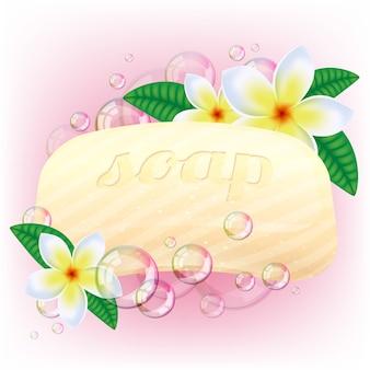Barra amarela do sabão com bolhas e flores brancas na cor-de-rosa.