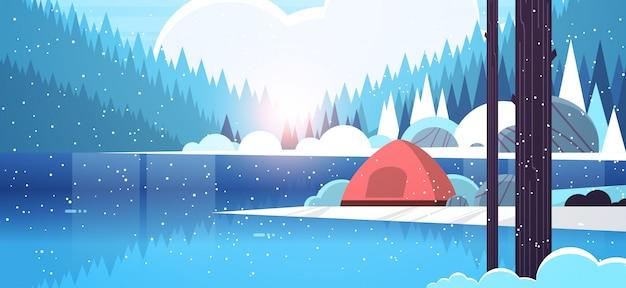 Barraca área de acampamento no acampamento da floresta perto do rio inverno acampamento curso férias conceito queda de neve nascer do sol paisagem natureza com água montanhas e colinas