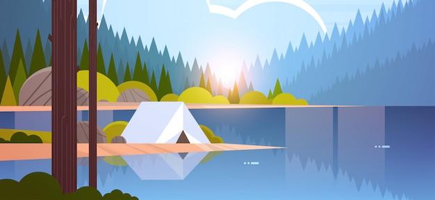 Barraca área de acampamento no acampamento da floresta perto do rio verão acampamento viagens férias conceito nascer do sol paisagem natureza com água montanhas e colinas