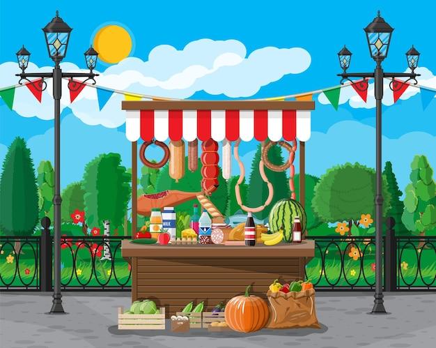 Barraca de comida de madeira do mercado tradicional cheia de comida com bandeiras, caixas. parque da cidade, lâmpada de rua e árvores. céu com nuvens e sol. tempo de lazer no parque da cidade de verão. estilo simples de ilustração vetorial