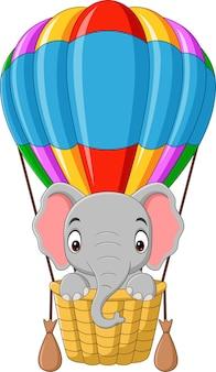Bebê elefante em desenho animado andando de balão de ar quente