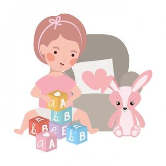 Bebê menina bonitinha com coelho recheado em caráter de sofá