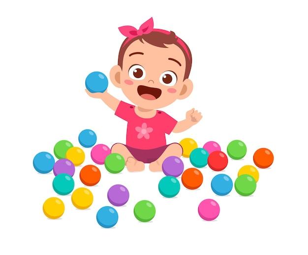 Bebezinha fofa brincando com bolas coloridas