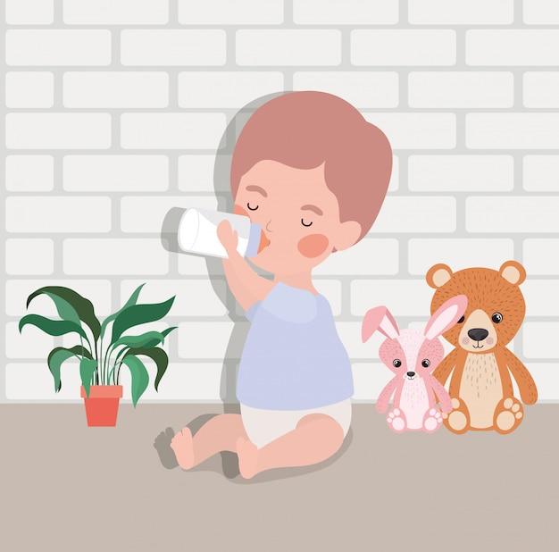 Bebezinho com leite de garrafa e brinquedos de pelúcia