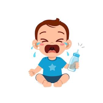 Bebezinho fofo chora segurando uma garrafa de leite vazia