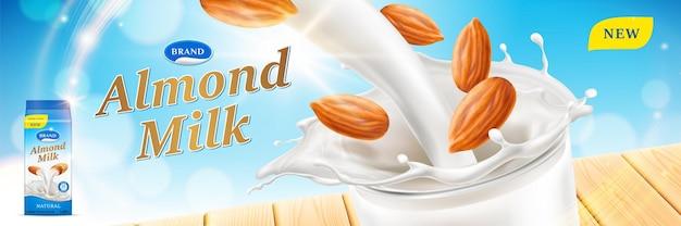 Bebidas de anúncios de leite de amêndoa derramando e respingando em copo de vidro isolado no fundo de bokeh do céu azul