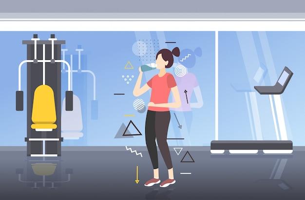 Bela aptidão atleta mulher beber água de garrafa de plástico após treino exercitar saudável estilo de vida moderno ginásio interior horizontal comprimento total